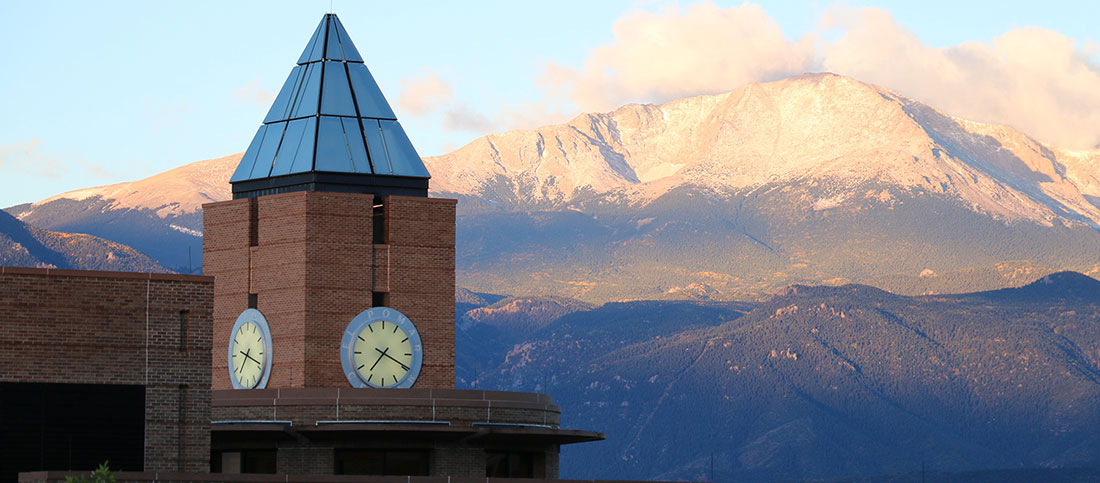 The mountains are visible behind the red-brick UCCS clocktower.